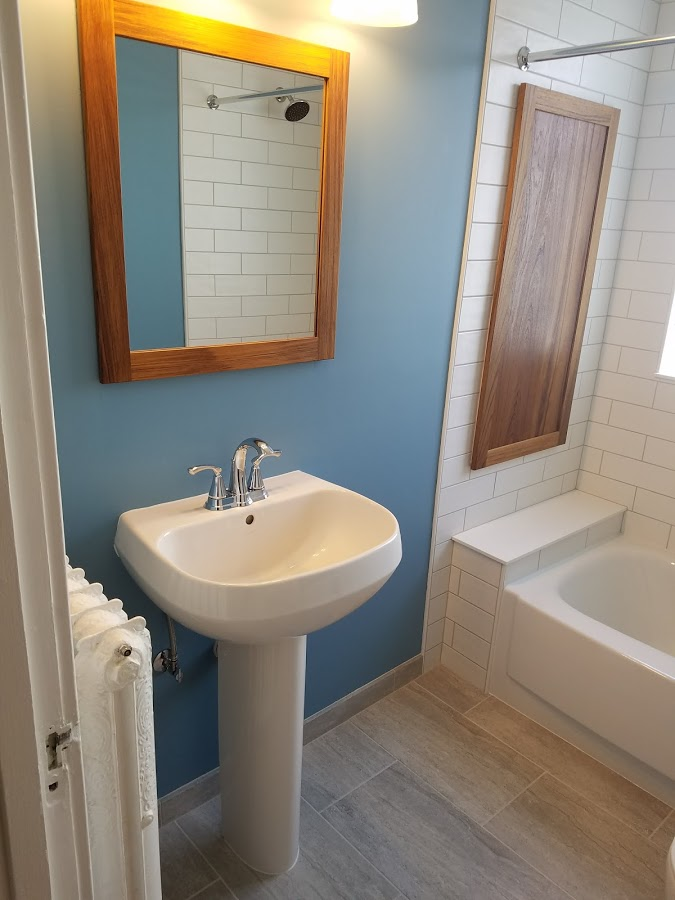 Bathroom with pedestal sink, teak cabinets and blue paint